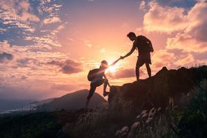 People Helping Each Other Hike up a Mountain at Sunrise. Giving a Helping Hand, and Active Fit Life