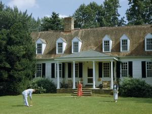People Play Croquet on Lawn in Front of Colonial-Era Estate