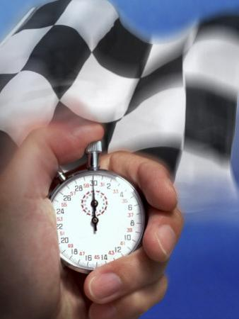 Person's Hand Holding a Stopwatch in Front of a Checkered Flag
