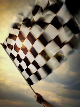 Person's Hand Waving a Checkered Flag
