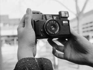 Person Taking Self-Portrait with Vintage Camera