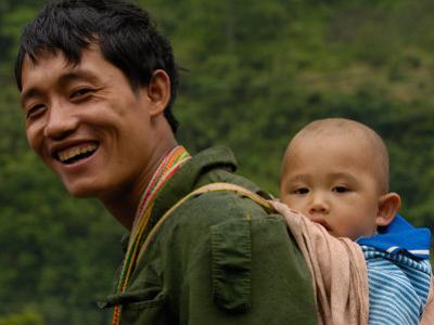 Black Lisu Carrying Baby at Market near Fugong, Nujiang Prefecture, Yunnan Province, China by Pete Oxford