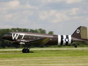 A Douglas Dc-3 in Military Paint Takes-Off from a Grass Airfield by Pete Ryan