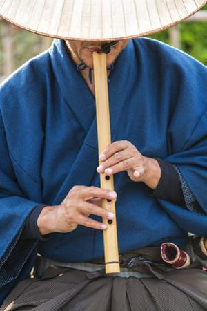 Japanese man playing traditional wooden flute, Kyoto, Japan by Peter Adams