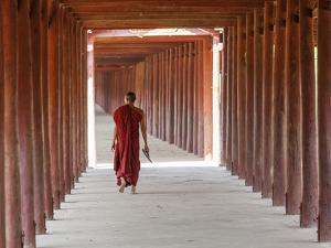 Monk in Walkway of Wooden Pillars To Temple, Salay, Myanmar (Burma) by Peter Adams