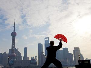 Practising Tai Chi with Fan, and Pudong Skyline, Early Morning, Shanghai, China by Peter Adams