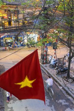 Vietnamese Flag and Street Scene, Hanoi, Vietnam by Peter Adams