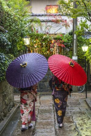 Women in traditional dress with umbrellas walking through Kyoto, Japan by Peter Adams