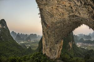 A Climber Scales Moon Hill, an Arch from the Remains of a Collapsed Cave by Peter Carsten
