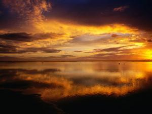 The Setting Sun Casts Light on Dark Clouds and Sea, Cook Islands by Peter Hendrie