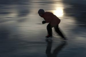 A Girl in Silhouette Skating on a Frozen Lake by Peter Mather