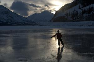 A Silhouetted Girl Skating on a Frozen Mountain Lake by Peter Mather