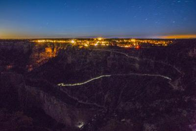 The Glow of a Few Head Lamps Forms a Bright Streak Beneath the Grand Canyon's South Rim by Peter Mcbride