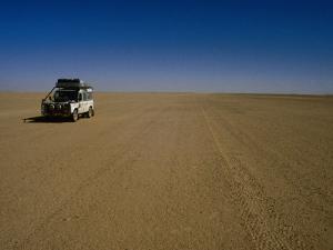 Car Crossing Sahara Desert, Algeria by Peter Ptschelinzew