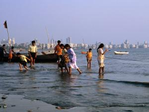 Locals Cooling off in Polluted Waters at Chowpatty Beach, Mumbai, India by Peter Ptschelinzew