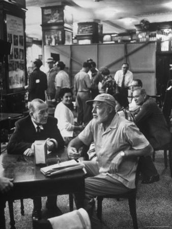 Noel Coward Chatting with Ernest Hemingway at Sloppy Joe's Bar by Peter Stackpole
