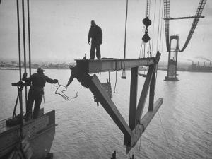 Raising the Truss, Men of the Raising Gang Ride the Swinging Steel 160 Feet Above the Water by Peter Stackpole