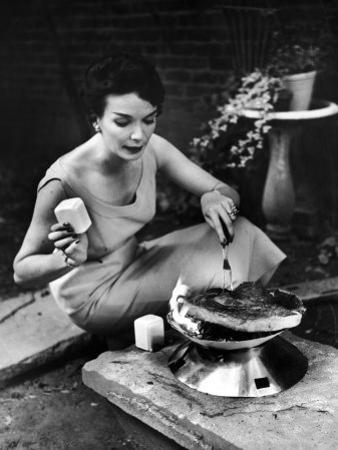 Well-Dressed Woman Cooking a Large Steak on the Aluminum Disposable Barbecue Grill by Peter Stackpole