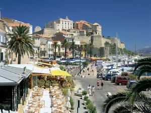 Restaurants in the Old Port with the Citadel in the Background, Calvi, Corsica by Peter Thompson