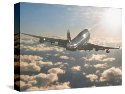 Jumbo Jet Above Clouds Into Sunlight