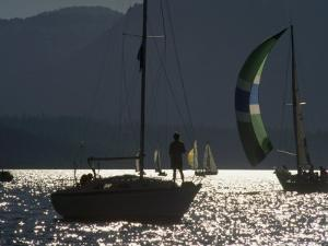 Backlit Boater Observes a Sailboat Race on Lake Tahoe, California by Phil Schermeister