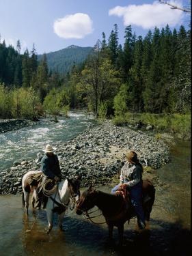 Horseback Riders Stand in Coffee Creek by Phil Schermeister