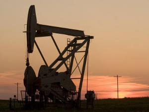 Oil Drilling Pump Silhouetted Against the Sunset in North Dakota by Phil Schermeister