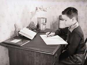 Boy Writing at Desk by Philip Gendreau