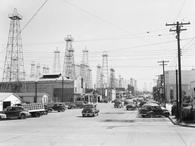 Clusters of Oil Derricks along Street by Philip Gendreau