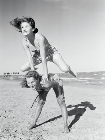 Girls Playing Leapfrog on Beach by Philip Gendreau