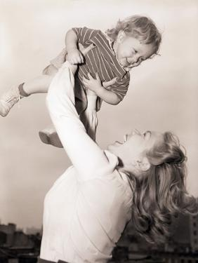 Mother Swinging Daughter up in the Air by Philip Gendreau