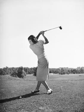 Woman Swinging Golf Club by Philip Gendreau