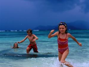 Children Running Out of Ocean in Stormy Weather, Seychelles by Philip & Karen Smith