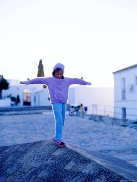 Girl Balancing on Edge, Caceres, Extremadura, Spain by Philip & Karen Smith