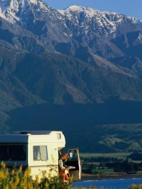 Woman Reading Map in Campervan with Mountain Behind, Kaikoura, New Zealand by Philip & Karen Smith