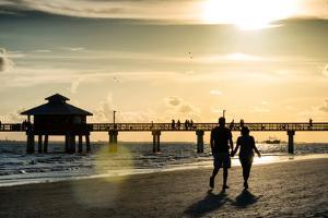 Loving Couple walking along the Beach at Sunset by Philippe Hugonnard