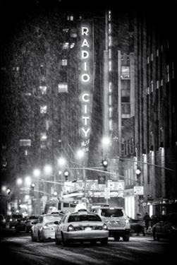 NYC Yellow Taxis in Manhattan under the Snow in front of the Radio City Music Hall by Philippe Hugonnard