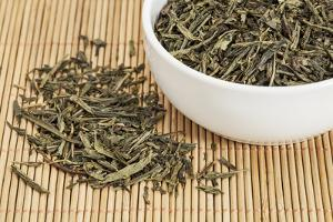 Loose Leaf Sencha Green Tea in a White China Cup and Spilled over Bamboo Mat by PixelsAway