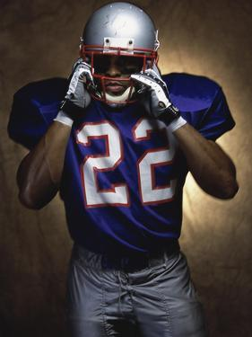 Portrait of an American Football Player Removing His Helmet