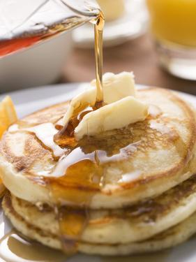 Pouring Maple Syrup over Pancakes with Dab of Butter