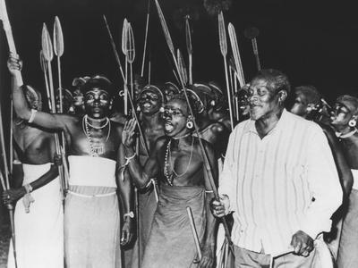 https://imgc.allpostersimages.com/img/posters/president-jomo-kenyatta-joined-in-tribal-dancing-of-the-rendille-tribe-at-embu-kenya_u-L-Q10WSIV0.jpg?artPerspective=n