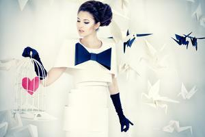 Art Fashion Photo of a Gorgeous Woman in Paper Dress Holding Birdcage with Red Heart. Black and Whi by prometeus