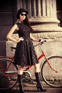 Beautiful Brunette Standing near Her Old Bicycle over City Background. Retro Style. by prometeus