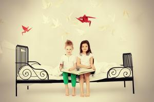 Cute Kids Sitting Together on the Bed and Reading Fairy Tales. Dream World. by prometeus