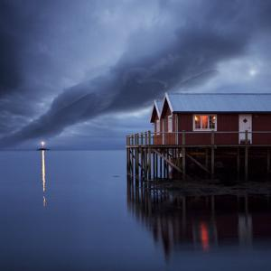 Rorbuer on Stilts at Dusk with Lighthouse, Lofoten Islands, Norway, Scandinavia, Europe by Purcell-Holmes