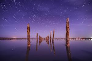 Poles in the Water at Night on a Background Star Trails by Q-lieb-in