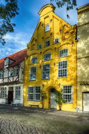 https://imgc.allpostersimages.com/img/posters/quaint-yellow-house-in-old-town-lubeck_u-L-Q1ASH810.jpg?p=0