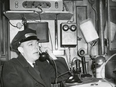 https://imgc.allpostersimages.com/img/posters/railroad-conductor-uses-an-on-board-telephone-to-communicate-with-other-parts-of-the-train_u-L-Q10WVI30.jpg?p=0