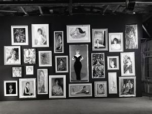 Actress Barbara Rush Posing in a Frame Cut-Out on a Wall Full of Paintings of Herself, 1960 by Ralph Crane