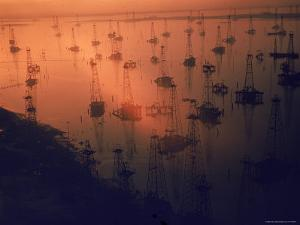 Oil Rigs Dating from the 1920's Dot the Shallows of Galveston Bay by Ralph Crane